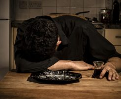 Sad and lonely man is resting his head on his dinner table in his kitchen and clutching a glass of wine
