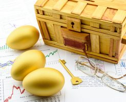 Three golden eggs and a golden key with a wooden chest on business and financial reports : Key success in sustainable growth investment concept